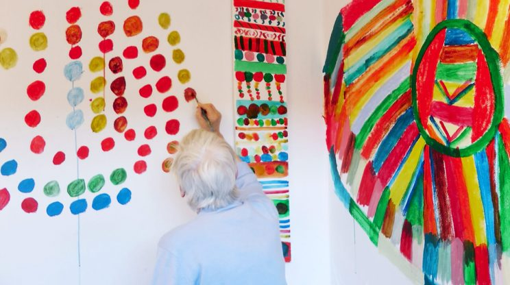 older women painting a vibrant abstract mural on a gallery wall in a care home.