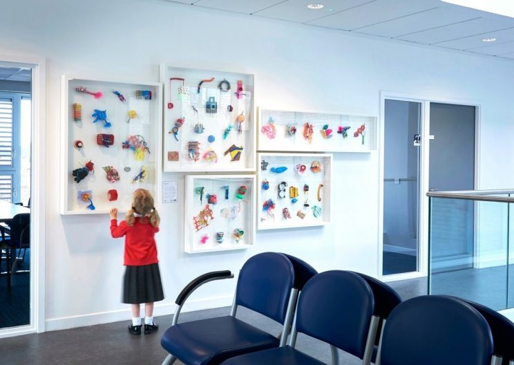 young child looking closely at framed art works in a hospital waiting area