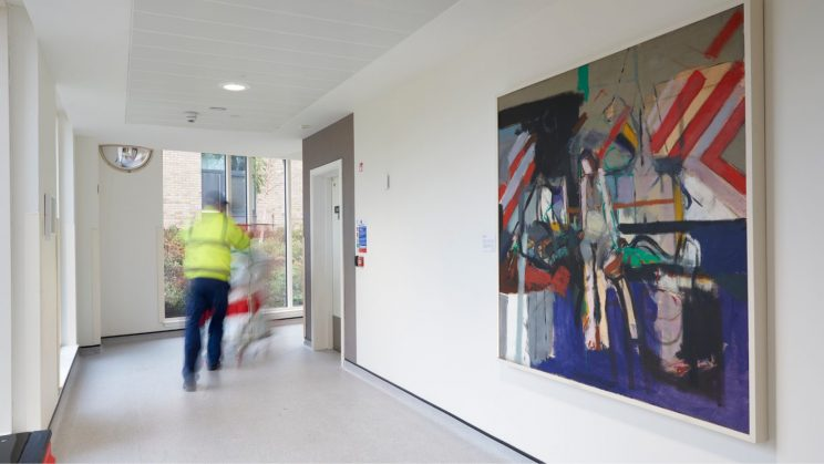 large artwork displayed in hospital corridor with a hospital porter pushinh a wheelchair past
